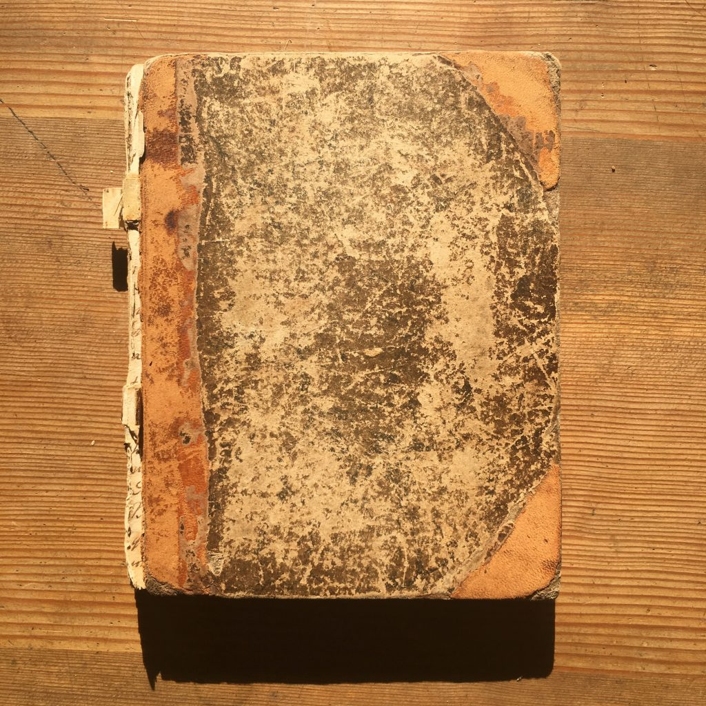 An old manuscript cookbook seen from the outside. It's an old book from the 1830s battered and fascinating.